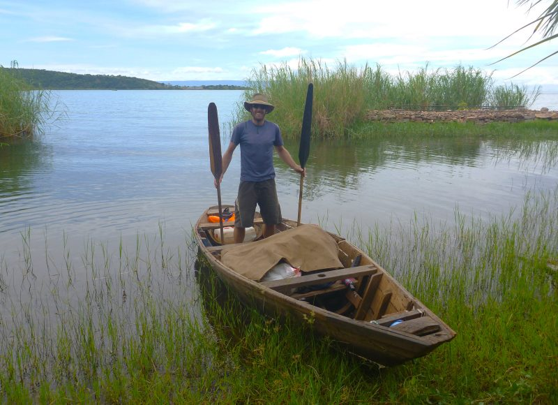 Minutes before setting off I posed with my unnamed craft outside of Kasanga, Tanzania. I had three paddles, all different, that I'd use as oars. I was ready to begin the adventure.