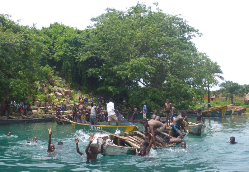From a distance I could hear a large group of people cheering, so naturally I went to have a look. What I found was a group of men, boats circled up, working together to pull up a large net full of fish. All the young boys of the village were there to watch and play, and everyone was very excited to see a strange white man show up.