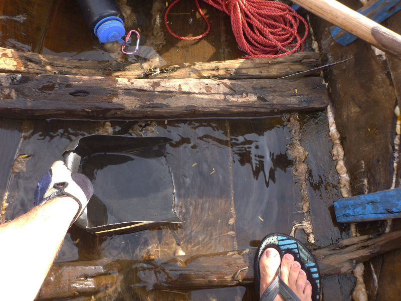Every few minutes I attended to the ritual of bailing out my leaky boat. Here you can also see the coil of cheap rope that I used to improvise a pair of oar locks. The rest I used to tie the boat to shore when I was unable to get it out of the water for the night.