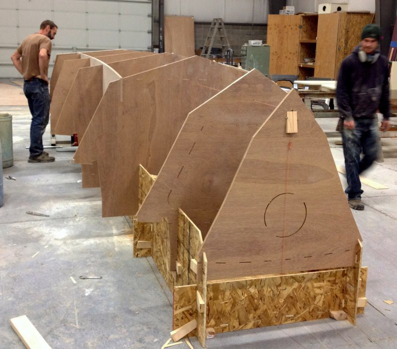 In the Devlin shop, the first Pelicano 20 takes shape on a form of interlocking pieces of oriented strand board. The plywood bulkheads and frames appear solid here, but openings, interior shapes, and deck and cabin-roof contours have been partially cut by the CNC router.