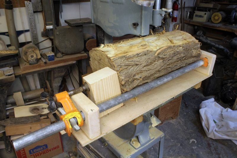 "This piece of locust was a bit long for the clamp in its normal configuration so I slipped the moveable part off and set it outside of the block. A bit of scrap wood bridges the gap. After I trimmed the bark from two sides, the log measured about 7 1/2"". To get enough clearance I removed the bandsaw's upper guide."