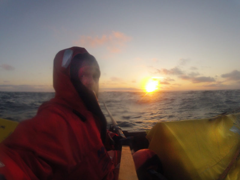 "Erik took this self-portrait at sunrise. The quarters were quite close with the ""cabin"" in the stern right at his feet. Erik, who stands about 6' 6"" tall, struggled to find a place to lie down and stretch out after his rowing shifts were over."
