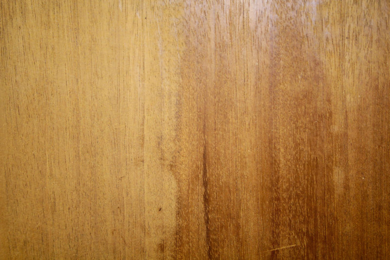 The left side of this mahogany board was sanded with a random-orbit sander with a 220-grit disk. The right side was smoothed with the Veritas Cabinet Scraper. The gloss is evident at top and the matte patches show that the the scraper is leveling the surface.