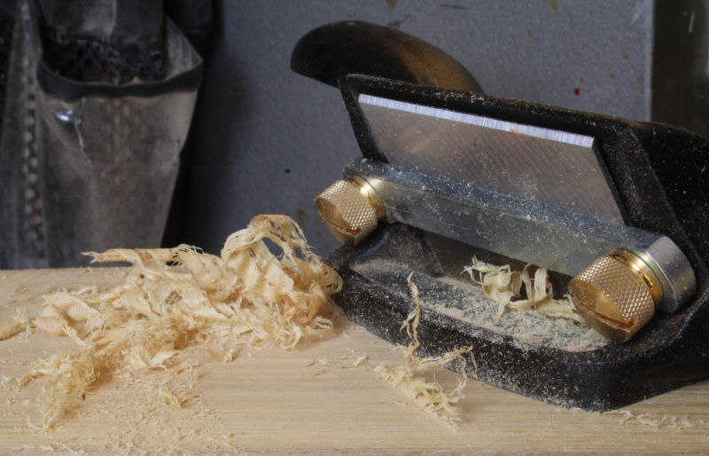 On this piece of locust the scraper produces shavings and some coarse dust.