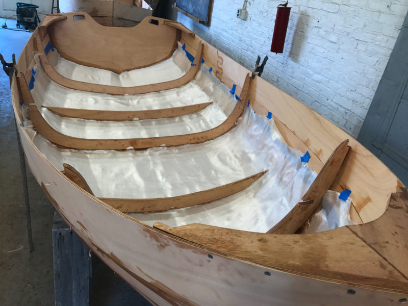 Fiberglass is cut into wide strips to fit between the frames. The glass on the inside covers five of the seven strakes; galls on the outside covers four.