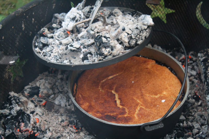 Set in the coals of a fire set in a steel fire box, an aluminum Dutch oven bakes a blueberry cobbler with the addition of heat from coals set on a lid with a rim.