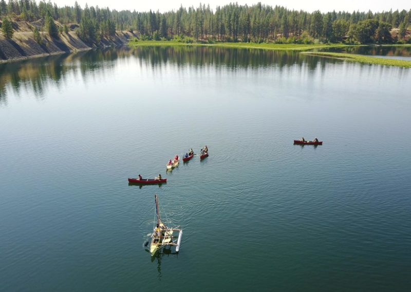 A sky-high view of fish lake, with canoes following the students' outrigger.