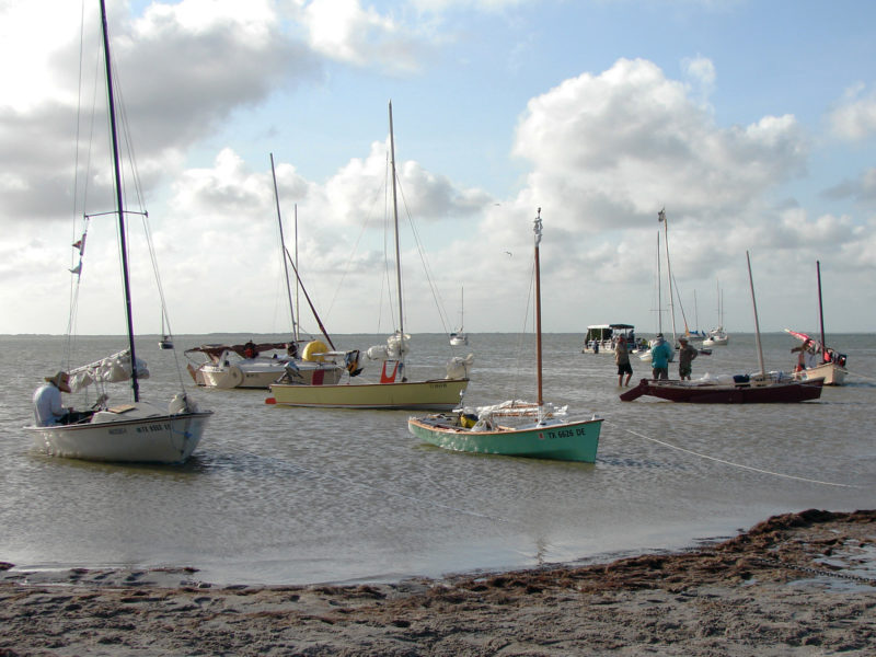 3. ARR & ARR rests on the bottom in only inches of water at Camp Two, on the west side of Padre Island, about halfway between Baffin and Corpus Christi Bays. Other Texas 200 boats here include a Bolger Dovekie (cream topsides and leeboard); a sloop designed and built by the late Joe Dobler (yellow topsides), renamed JOE COOL by its current owner; and a couple of Jim Michalak-designed Mayflies (dark brown boat and tan boat at right).