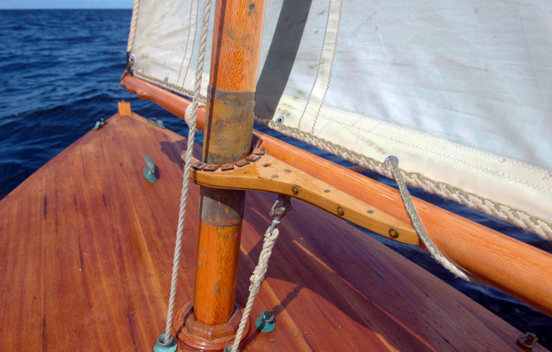 A half jaw is used instead of a parrel to keep the boom tight to the mast.