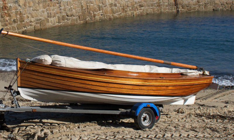 The dinghy's bottom has brass half-oval along the keel and bilge guards to protect the hull on the beach.