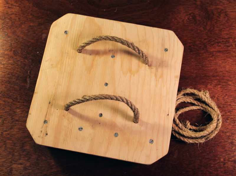 "The 1/2"" manila loops are set at a boot's width and each loop, requiring about 2' of line, is laced through holes drilled 6"" apart. The lacing line, coiled up here, is about 6' of 1/4"" manila with a half hitch in each end to keep it from unravelling. The base is made of 1/2"" plywood, the same as I used for my 14"" pattens. My other 12"" pattens have a base of 3/4"" pine."