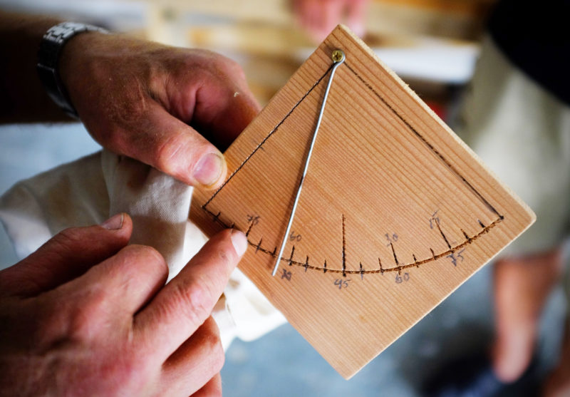 One of Ulf's handmade instruments, a båtlodd, measures the angles of the planks. Much of the shaping of the boat was done by eye and feel rather than precise measurements.