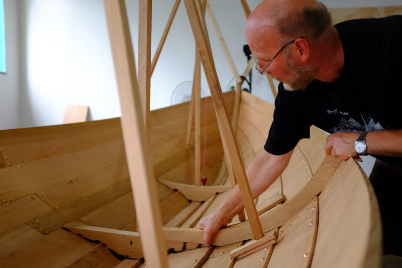 Ulf fits the first of the frames. The small gaps outside of the frame at the keel and the plank laps allow water to pass through.