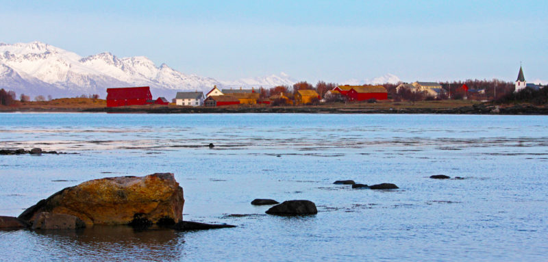 The village of Kjerringøy is nestled among the fjords and coastal mountains of the north central Norwegian coast. The red and white buildings on the left are part of the Kjerringøy Museum and Old Trading Post