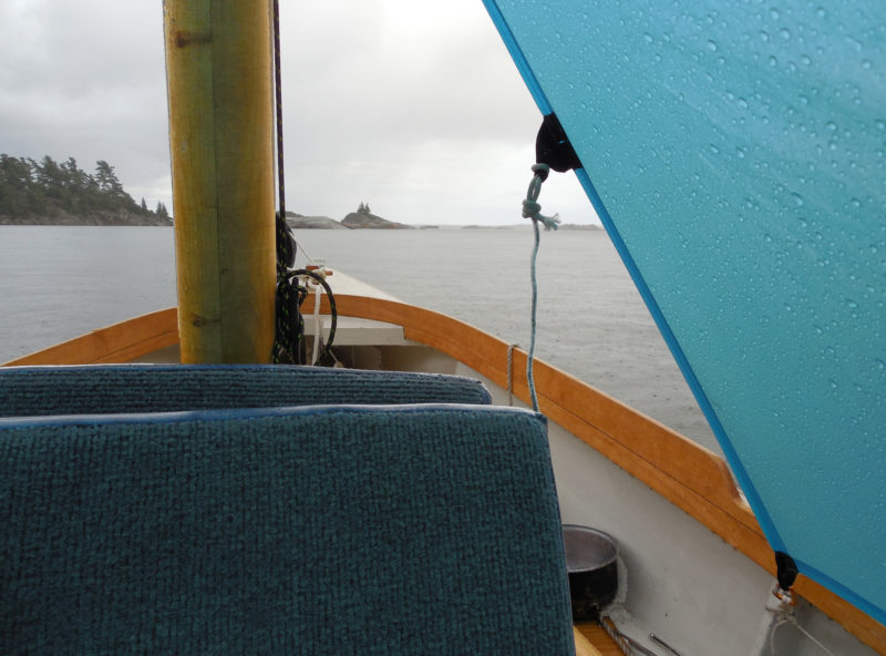 I left my malfunctioning VHF radio in the car and returned to simpler methods of weather forecasting for this cruise—methods as simple as hearing the patter of raindrops overhead. An improvised boat tent and plenty of books helped me wait out the rain at South Benjamin Island.