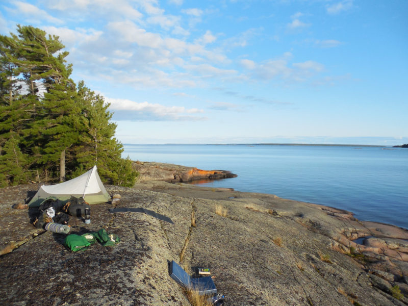 Fox Island's rugged southern shores offer plenty of good campsites overlooking the water, and a pleasant break from sleeping aboard. Here the view is east toward Amedroz Island and the Bay of Islands beyond.