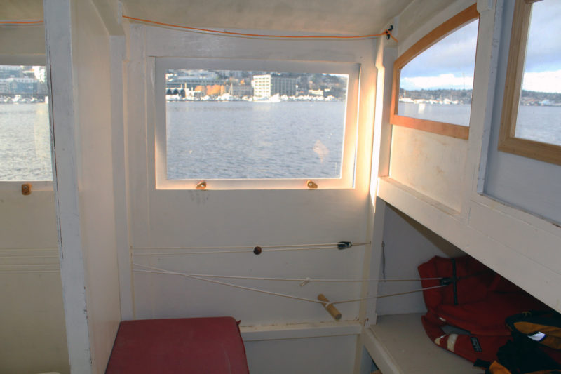 What was originally the boat's sleeping quarters now serves as the pilothouse when underway in foul weather. The orange line at the top is connected to the kill switch, the line just below the window with the wooden bead controls the throttle, and the line at the bottom with the dowel attached operates the tiller. The plywood panel that is part of the sleeping platform has been temporarily replaced by a smaller piece that leaves an opening for a foot well.