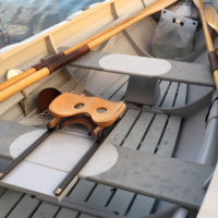 The sliding seat rig, spanning a thwart in the author's dory, has shorter tracks than those used in racing shells, but is well suited to using the same oars and locks that are used for fixed-seat rowing. Note the foot brace secured to the floorboards under the aft thwart.