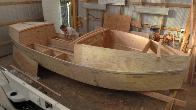 "Koen works on storage compartments in the cockpit. The bottom, bulkheads, transom and foredeck were made with 5/8"" fir plywood and 3/8"" plywood used for the rest. The lumber for the building jig was later transformed in four oars."