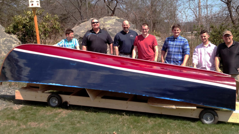 The Burns sons and grandsons gathered for moving the hull out of the cellar on its wheeled building frame.
