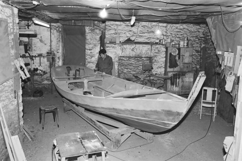 John Elliott and his brother Doug built this wooden Drascombe Lugger in their boatshop in 1978. The building at Yealmbridge in Devon, England, was 300-year-old flocking mill and furniture factory that was cold and draughty in the winter. The boat was built for the Rees family and named REESKIP (Rees' ship) has spent all her life in Holland. A later owner renamed the boat ELLIOTT in honor of the builders after John passed away. The boat was built from BS1088 mahogany marine plywood and iroko hardwood with an all glued construction using phenolic resin adhesives. In the photo, John is fitting the deck beams prior to the decks and sheer strake and transom return being added. The hulls were built upside down on a jig on the floor above, then removed from the jig, turned right side up and the build continued on the ground floor. Every Lugger the Elliotts built was an individual custom build, so no two were identical.