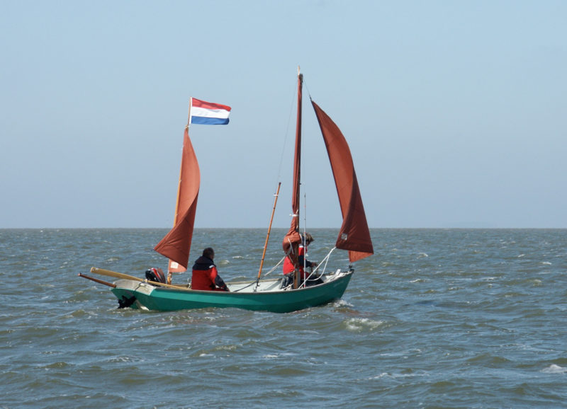 The 1982 Lugger CASTOR & POLLUX takes it easy flying only the jib and mizzen. The Dutch owner installed a tabernacle on the main mast to make it easier to lower. One of the oars is set in a transom-mounted oarlock in anticipation of shallow water ahead. The oar can be used for steering when the rudder needs to be retracted in thin water.
