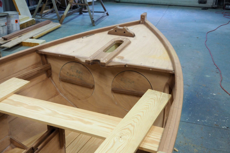 The forward watertight compartment is accessed through two hatches because it is partially divided by a box for the forward mast partner and step. The aft mast partner is open; the mast will be lashed to eyelets yet to be installed.