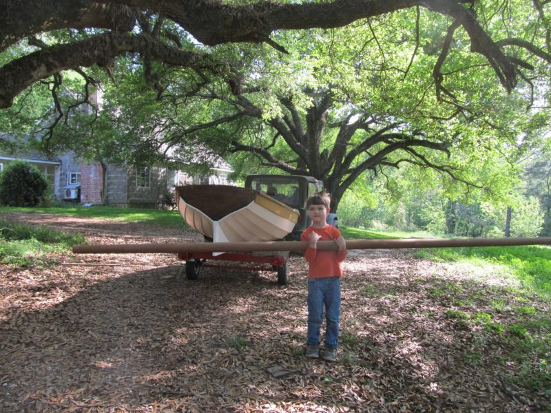 Patrick holds up the mast. The boat is ready for its debugging period in the local oxbow.