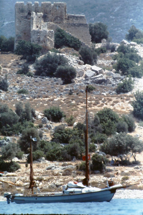 Rising above LEGOLAS are ruins near the village of Lindos, on Rhodes, the the largest of Greece's Dodecanese islands. August, 1982.