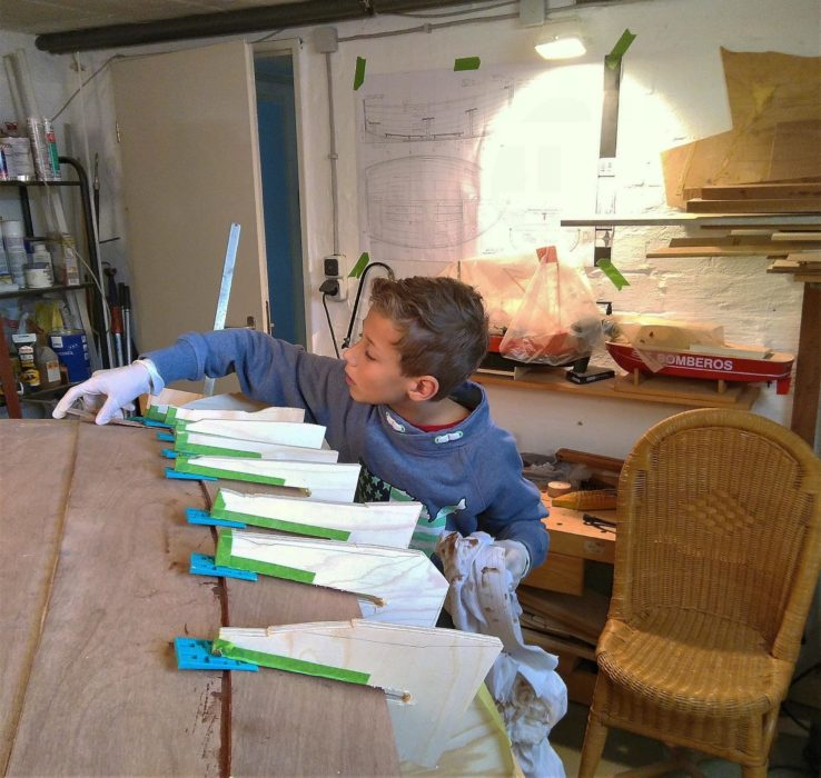 Tristan often pitched in on the construction. Here he's cleaning up excess thickened epoxy after a plank has been secured in place with homemade plywood clamps and wedges.