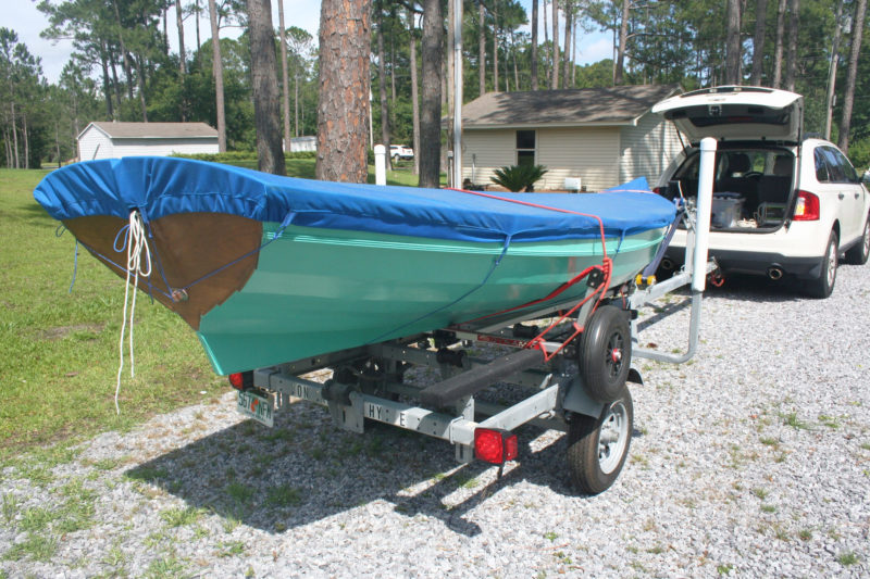 A boat and its dolly can ride on a trailer for the drive to the beach, and dragged off for the walk to the water. This dolly rests its axle on the trailer's bunks. Some trailers can be modified with supports for tha dolly's wheels.