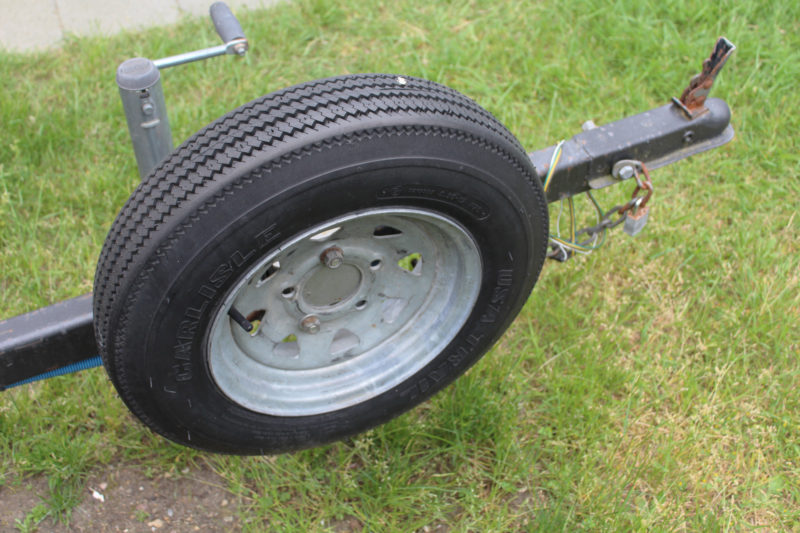 """This trailer tire looks brand new—it still has all of the little rubber """"hairs"""" left by the the mold that created it—but the codes molded into the sidewall indicate it is 16 years old. It needs to be replaced."""