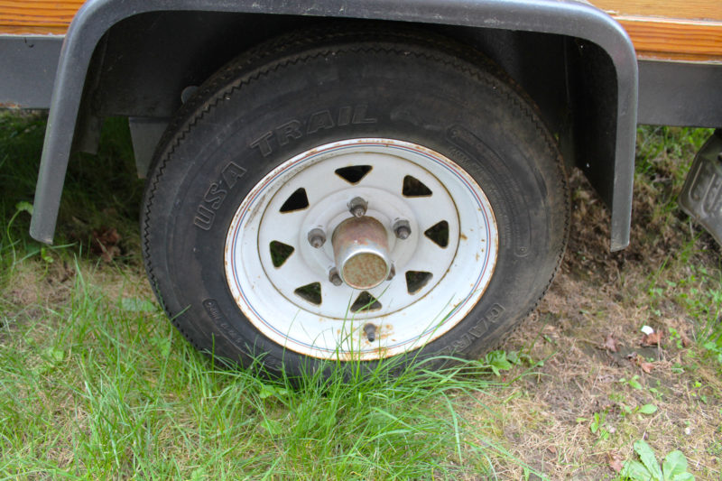 If the only spot you have for your trailer is in the back yard, roll the tires up on concrete pavers to keep the moisture in the grass and soil from hastening the degradation of the rubber.