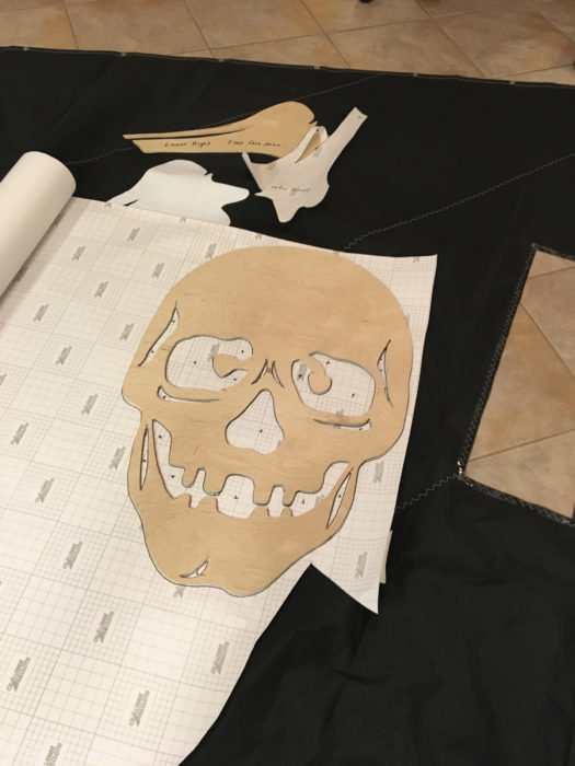 The wooden pattern for the skull sits on the backside of the white insignia cloth, ready to be traced. The cloth's removable backing, marked with a grid, is removed to expose the adhesive.