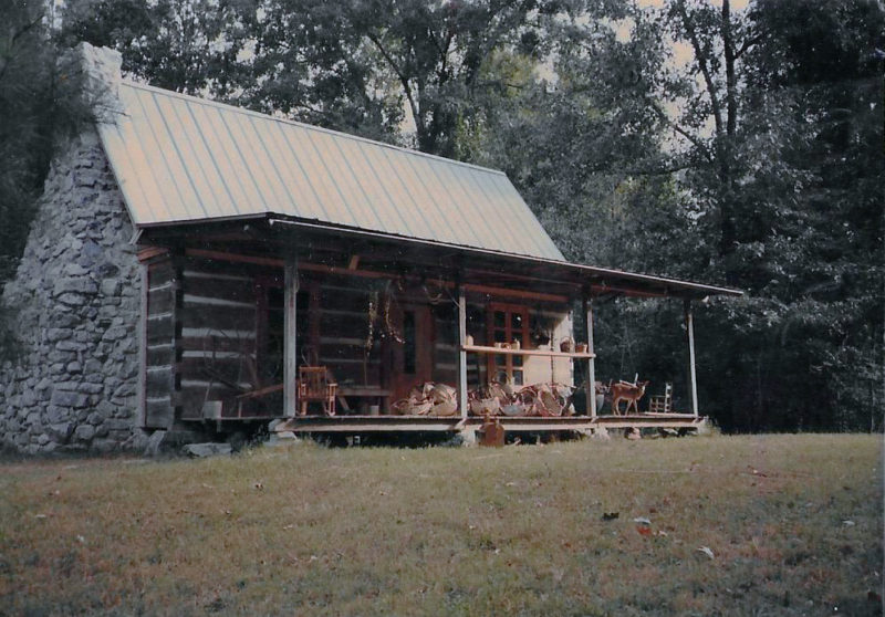 From the cypress logs to the stone chimney, Dad built every inch of the cabin where I spent my childhood. Mom's baskets are piled on the front porch and my pet deer is visible next to them. The baskets went to the fair, the deer did not.