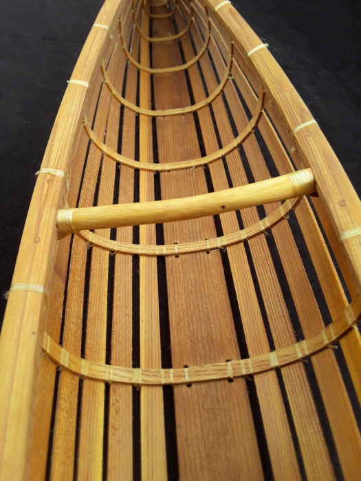 The thwart, shown here in the model, is made from a barked sapling with its ends thinned and wrapped around the inwale. The long tail ends are then lashed to the bottom of the thwart.