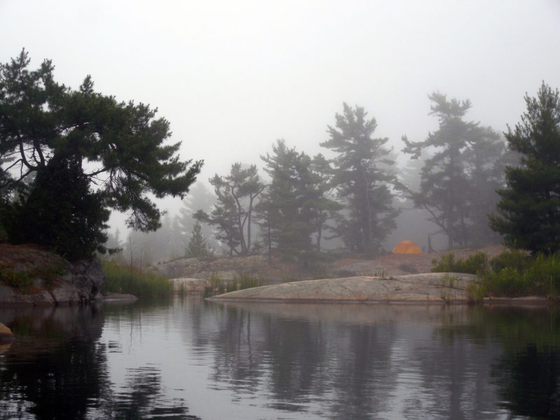 """The pond behind my Tanvat Island campsite—you can see my yellow tent through the fog—was too shallow for the boat's 7"""" draft, and the entrance too narrow for the hull. It was a rare dead end."""