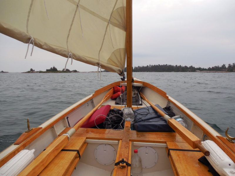 My fourth day began with cold rain and a strong breeze. Fortunately, the boat's boomless standing lugsail is easily reefed: simply roll up the foot and tie it in place. With the first or second reef tied in, the boat performs well to windward; the deep third reef keeps things in control when running for shelter.