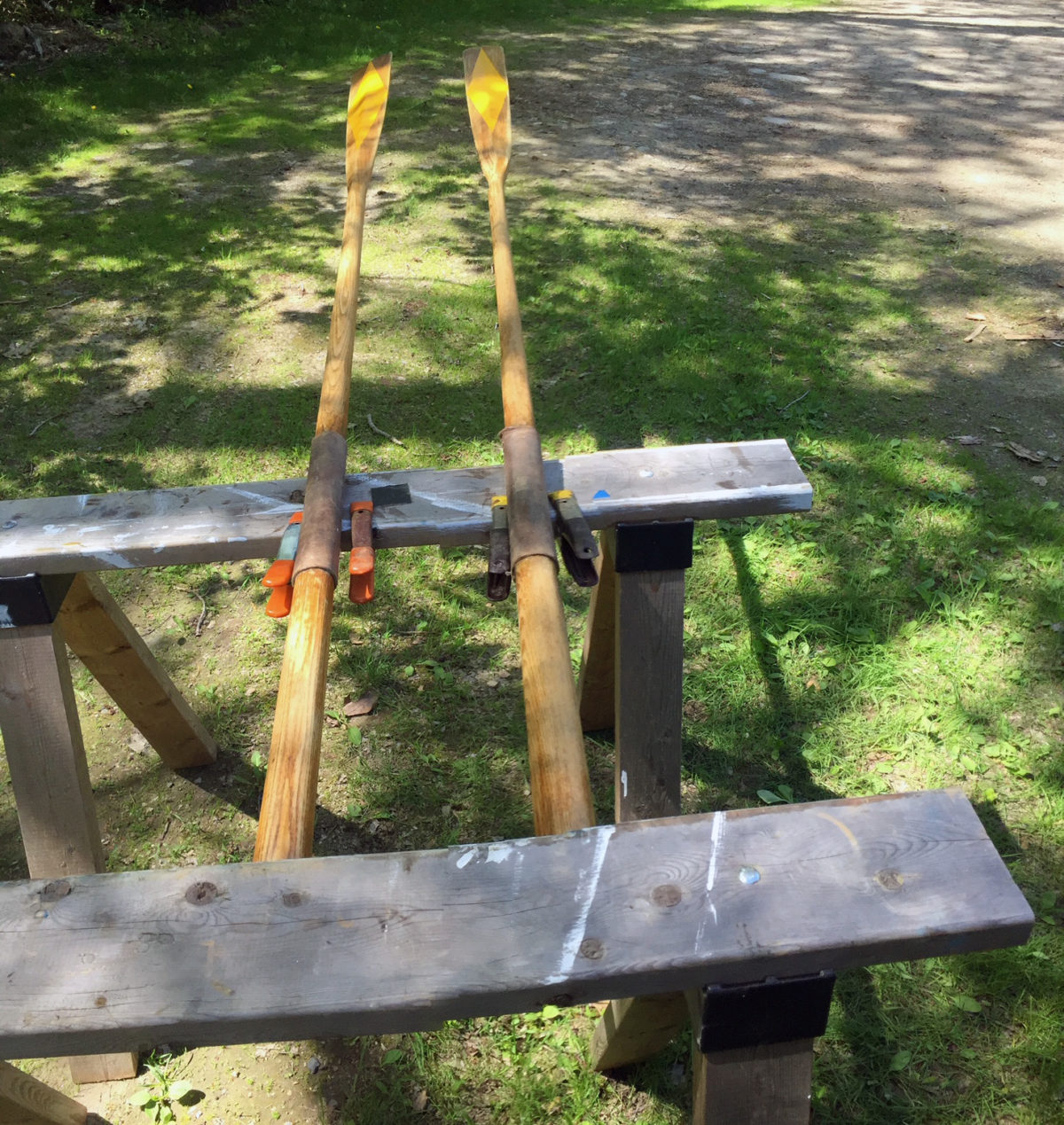 A pair of sawhorses make contact with the handles and the leathers, leaving the rest of the oars free for varnishing.