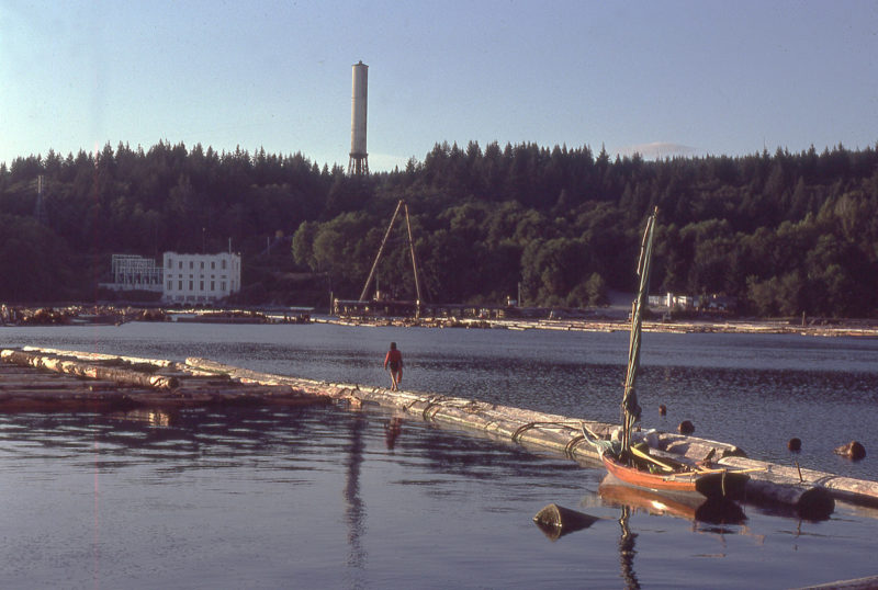 Log booms made the cove at Stillwater an especially quiet anchorage. On the north side of the cove is a hydro power plant built in the 1920s. The tall structure is a surge tower that regulates the water pressure in the 1-1/2-mile long pipeline from Lois Lake to the power plant.