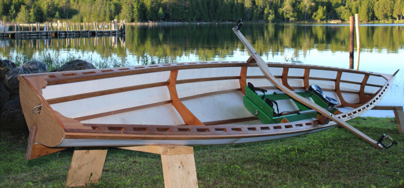The author's Ruth is rigged with a homebuilt rowing rig for solo rowing and is without floorboards and a seat for a passenger. A False transom covers the edges of the fabric skin for a tidier appearance.