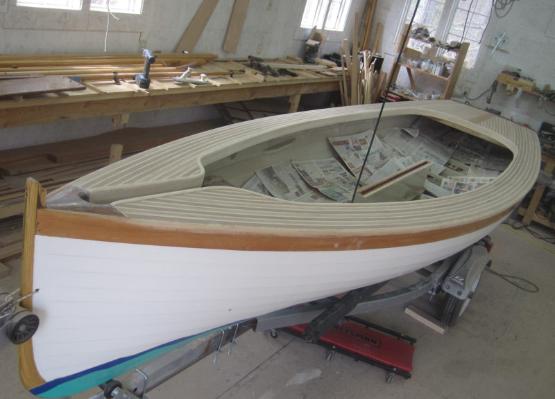 The slotted foredeck makes mast raising easy. For trailering, the spars all fit inside the boat by tucking one end under the aft deck and slipping the other down through the slot.
