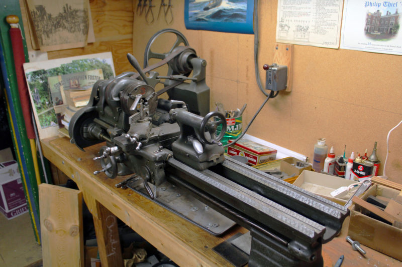 "Phil bought this machinist's lathe, used, on November 24, 1987. It's a South Bend C9-10JR, manufactured in South Bend, Indiana. Its original owner purchased it in 1949. The headstock needed some work and a few parts were missing, so Phil wrote to the manufacturer on January 9, 1988: ""Ladies and Gentlemen, I have recently achieved a life-long ambition and at age 67, a few weeks before retirement from teaching, acquired a South Bend Lathe."" The motor, here hidden from view, delivers power to the lathe with a flat leather belt, seen on a three-step pulley."