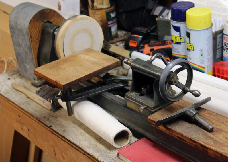 For woodturning projects has a small lathe driven by a motor mounted underneath the workbench. Here it has a sanding disc attached to the headstock and a wooden table on the tool rest. Hi youngest daughter has fond childhood memories of spending time in the shop using this lathe.