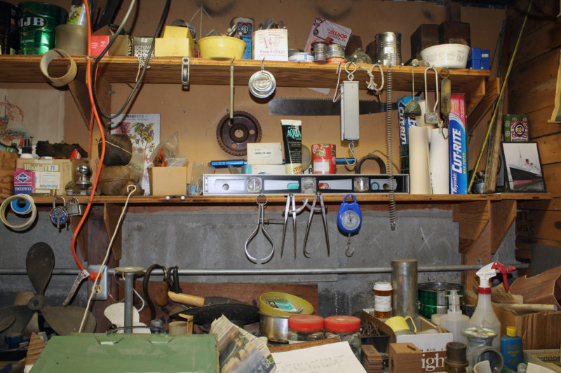 "You could say Phil's shop is ""organically"" organized. His tools and materials aren't separated into categories, they're intertwined like the roots of a tree, and juxtapositions like waxed paper, an old brass scale, and a padlock, or tarred marline, a trailer ball, and toothpicks have a natural, even poetic quality. Over his home's front door, there is a sentence, one of many written on the dark exposed ceiling beams in all caps in white chalk, that reads: ""A LOT OF WHAT I DO GROWS OUT OF WHAT I'M DOING."" The shop fosters unexpected possibilities and is fertile ground for the imagination."