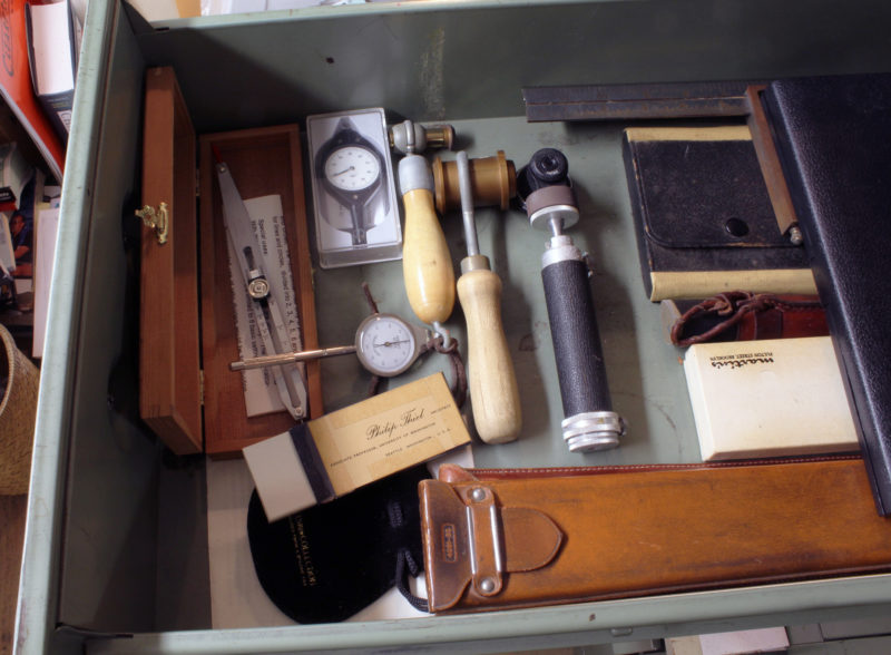 Phil kept the tools he treasured most in a locked file cabinet. This is the first time the draw has been opened since his passing. In the wooden box to the left is a proportional divider. To its right are two dial opisomters, or curvimeters, for measuring lengths long curved lines. I don't know what the three devices with handles are. The black one to the right, made by Nikkor, has a lens that provides a fisheye view. The two with wooden handles are Phil's home-made versions using wide-angle door viewers for lenses. The leather case at the bottom holds one of many slide rules.