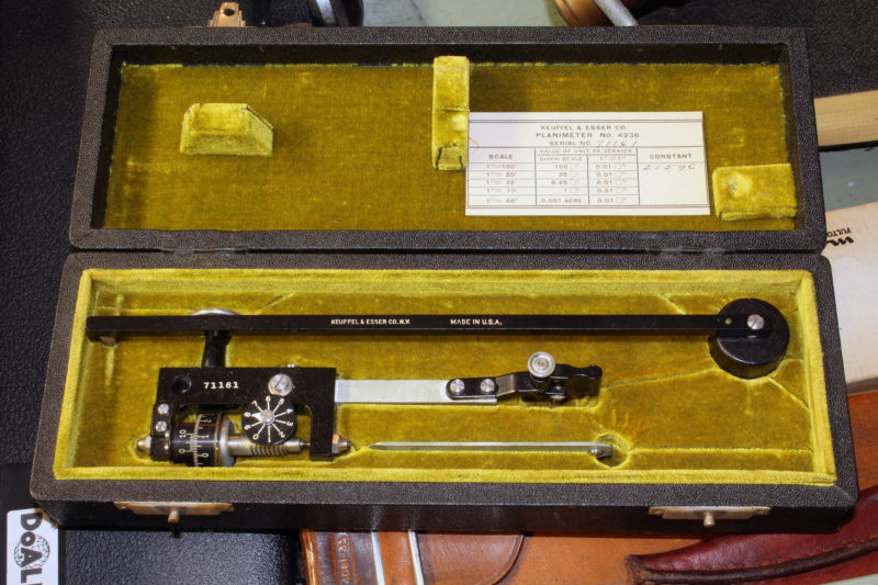 I only knew what this was because I passed down from my grandfather, a civil engineer. It's a polar planimeter used to measure the area of shapes on a drawing. The top arm has a pin with a weighted disk to hold it in place. The other arm has a pointer that is used to trace the shape. The cylinder on the lower left has a polished steel wheel that both rolls and slides as the pointer moves. By some miracle, the area shows on the scale when the outline is complete. The planimeter can be used in boat design, for example, to measure the areas of hull cross sections.