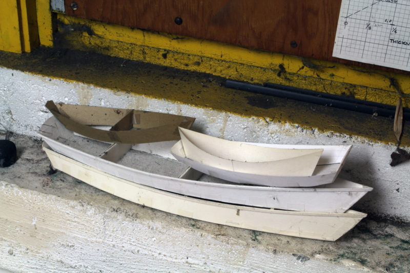 "Sitting on ledge near the drafting table is a stack of paper models: a tombstone-transom dory at left and a double ender sitting in a pram. The two at the bottom are for the 5' 7"" Skiffcycle, one of the smallest of Phil's ""pedal-powered boats for the flâneur-afloat"" and designed for a commercial Sea-Cycle drive. Phil's graph plotting boat speed and pedal rpm shows the Skiffcycle reaching 5 1/2 mph, though Phil, a flâneur himself, wouldn't dream of rushing about at such a pace, missing all of the sights, sounds, and scents to be taken in at a more leisurely pace. On at least one occasion, he furrowed his brow when I told him I usually paddled my kayak at 6 mph."