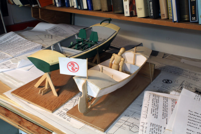 "Models for the 15' 4"" Aphasia (left), designed in 2006, and the 12' 4"" Sanpram, designed in 2011, are resting on drawings for the Escargot. The Center for Wooden Boats in Seattle has had the first-built Aphasia in its rental fleet for many years and it is fleet's most popular boat. It is equipped with two Sea-Cycle pedal drives, making the boat extremely maneuverable. With one drive pedaled forward and he other in reverse, it can spin around in its own length. The Sea Cycle drives are expensive, so for the Sanpram Phil designed a drive for the do-it-yourselfer. Bicycle pedals and cranks turn large pulleys and V-belts transfer the power to a small pulley and an idler on the propeller shaft. The propeller is made of stacked plywood, like the one on the workbench."