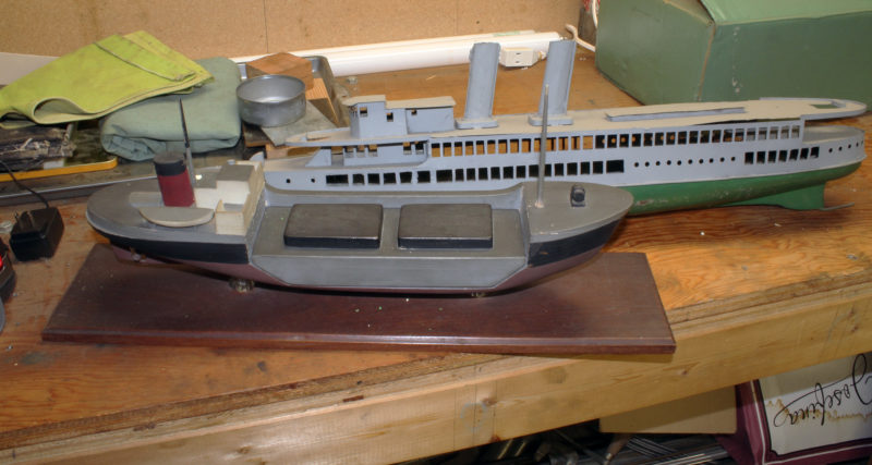 Among the models in the shop is a steel passenger ship of unknown origin and a freighter with a nesting barge. As I recall from my conversations with Phil, he designed the freighter while working as a naval architect. The idea was to create a system where cargo carried by two different means did have to be reloaded. It's like the freight trains that carry trailers or containers that are also hauled by truck or by ship. A barge used for inland waters could be floated aboard a purpose-built sea-going vessel.